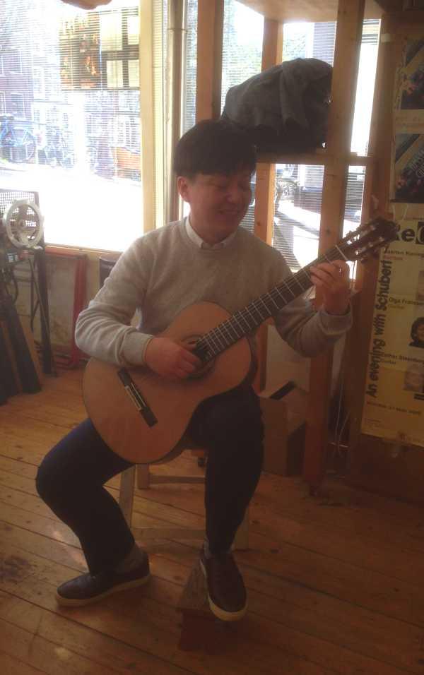 minsu yu playing guitar in otto vowinkel's workshop