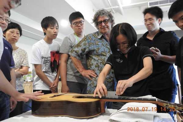 Malaysian guitarist Hong Tee checking the frets of her guitar.